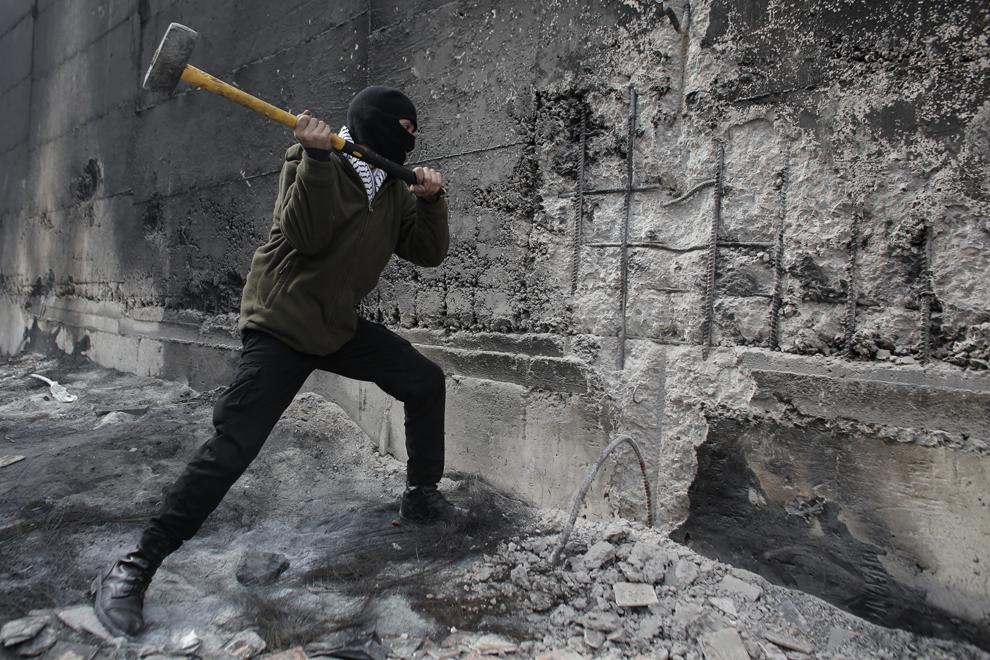 Un protestatar palestinian loveşte cu un ciocan bariera controversată ce separă oraşul Abu Dis din Cisiordania de Ierusalim, luni, 17 noiembrie 2014.