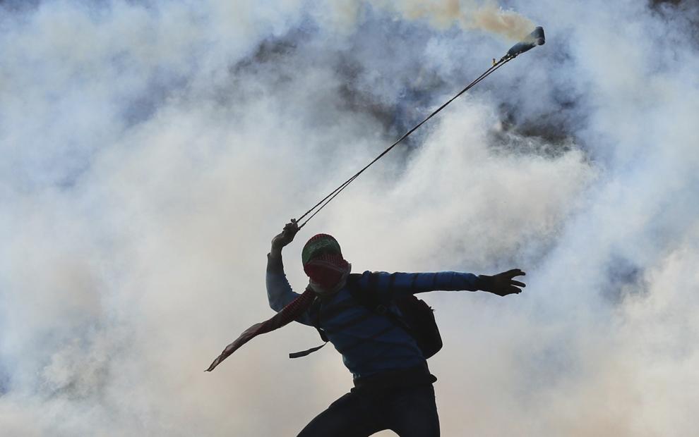 Un tânăr mascat ce poartă o banderolă Hamas foloseşte o praştie pentru a arunca o canistră de gaze lacrimogene înspre forţele israeliene, în timpul unui protest în apropiere de Ramallah, Cisiordania, marţi, 18 noiembrie 2014.