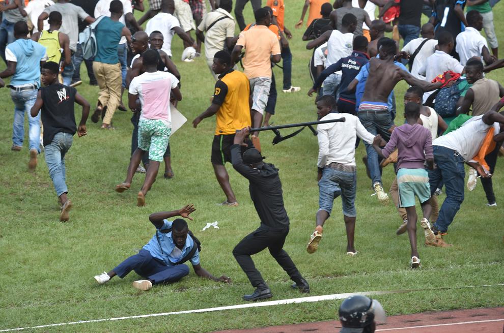 Un poliţist loveşte un bărbat după ce suporterii au intrat pe teren la finalul meciului de fotbal dintre naţionala Coastei de Fildeş şi cea a Camerunului din cadrul grupei D a Cupei Africii pe Naţiuni, miercuri, 19 noiembrie 2014.