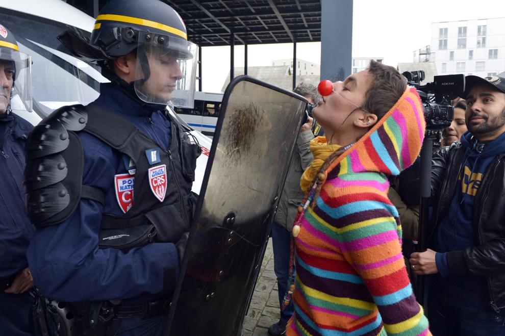 O tânără protestează în faţa unui jandarm ce pazeşte Palatul de Justiţie (Tribunalul) din Nantes, Franţa, sâmbătă, 22 noiembrie 2014.