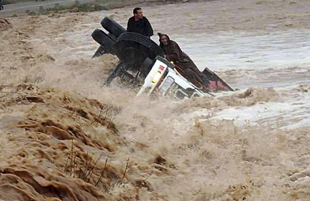 Şoferi sunt izolaţi pe un camion răsturnat de o inundaţie, în sudul regiunii Quarzazate, Maroc, sâmbătă, 22 noiembrie 2014.