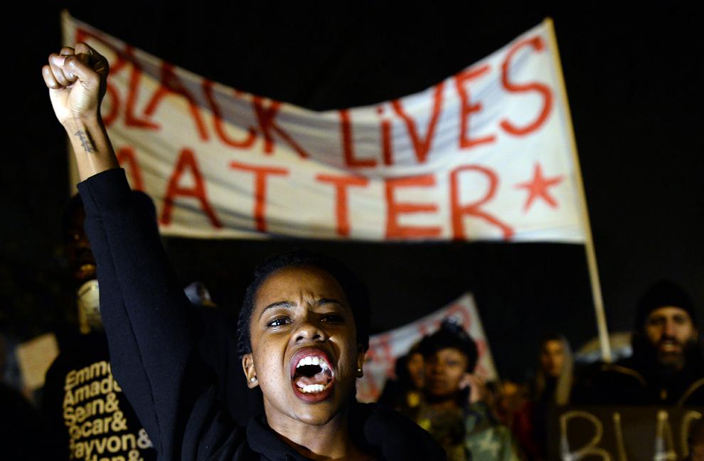 Protestatari strigă sloganuri în timpul unei demonstraţii, în St. Louis, Missouri, duminică 23 noiembrie 2014.