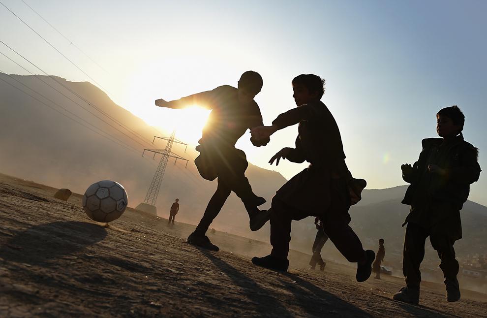 Copii afgani joacă fotbal pe un teren în Kabul, Afganistan, duminică, 23 noiembrie 2014.