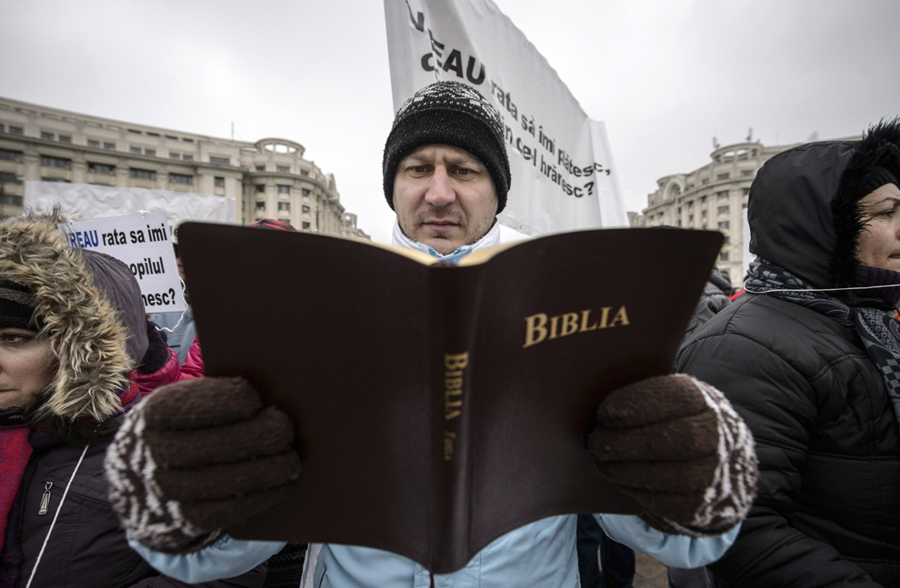 Un bărbat se preface că citeşte Biblia în timpul unui miting de protest, organizat de Grupul Clienţilor cu Credite în CHF, prin care se solicită conversia creditelor din valută în lei, în Bucureşti, duminică, 8 februarie 2015.