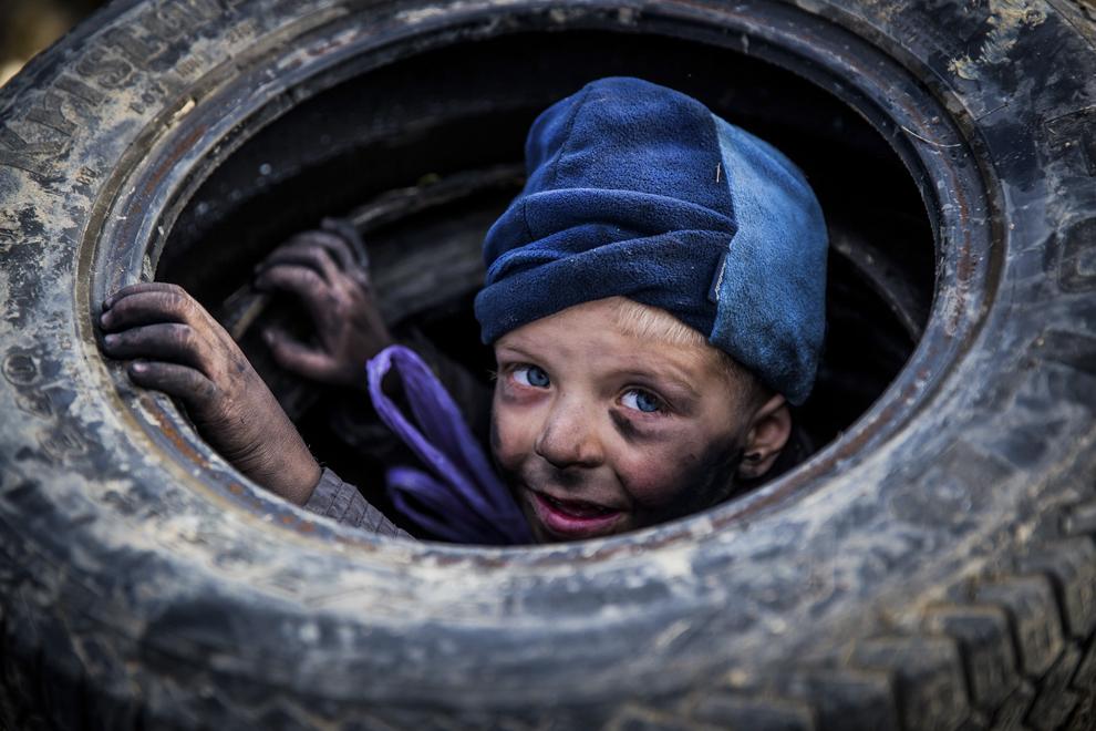 Un copil aşteaptă să dea foc unor cauciucuri, în noaptea Lăsatului de Sec, ultima zi dinaintea postului Paştelui, pe dealul de lângă comuna Poplaca, judeţul Sibiu, duminică, 22 februarie 2015. Tinerii dau foc cauciucurilor şi le rotesc în aer, strigând numele celor care şi-au întemeiat familii de curând sau al celor care s-au despărţit. Acest obicei are loc în mai multe sate din Mărginimea Sibiului şi reprezintă un dialog între grupurile de tineri.