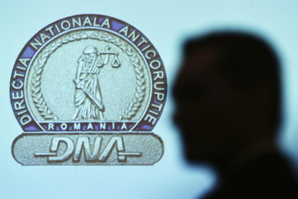 Umbra unei persoane este proiectată pe un panou cu sigla Direcţiei Naţionale Anticorupţie (DNA), în timpul evenimentului de prezentare a Raportului anual de activitate al instituţiei pe anul 2014, în Bucureşti, marţi, 24 februarie 2015.