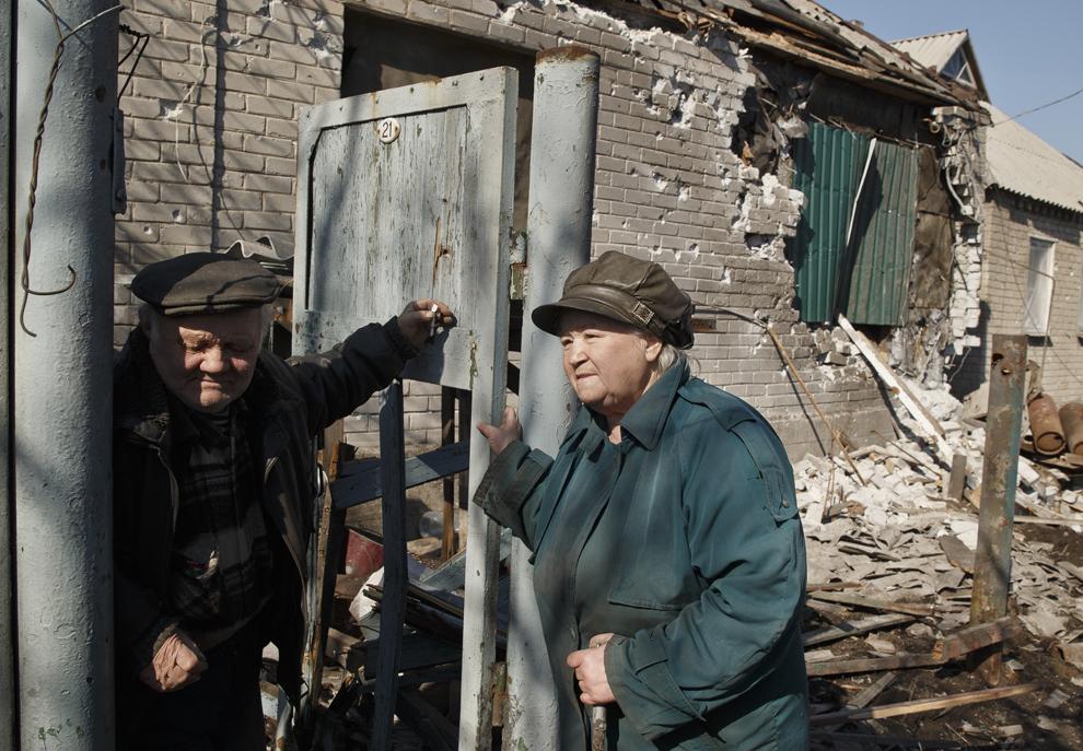 """Un cuplu în vârstă sta în faţa casei lor grav avariate, în Debaltseve, Ucraina, luni, 9 martie 2015. Mai mult de 6.000 de oameni au murit în estul Ucrainei de la începutul conflictului, cel care a dus la o """"devastare nemiloasă de vieţi ale populaiei civile şi a infrastructurii"""", potrivit biroului ONU pentru drepturile omului."""
