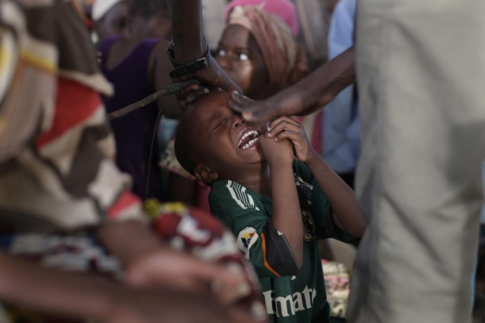 Un copil plânge după ce a fost lovit în ochi de către profesor, în timp ce elevele recită versete din Coran, într-o madrasa (şcoală religioasă) improvizată în tabăra de refugiaţi Zafaye, situată la aproximativ 15 kilometri de centrul oraşului N'djamena, Ciad, miercuri, 11 martie 2015.