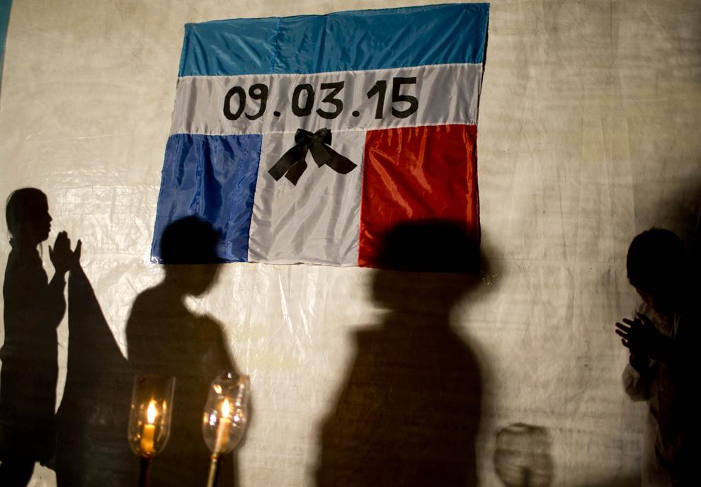 Umbrele unor copii pot fi văzute pe o prelată pe care sunt expuse steagurile combinate ale Argentinei şi Franţei împreună cu data la care a avut loc accindentul de elicopter, în timpul unui marş al tăcerii ţinut în memoria victimelor, în Villa Castelli, Argentina, joi, 12 martie 2015.