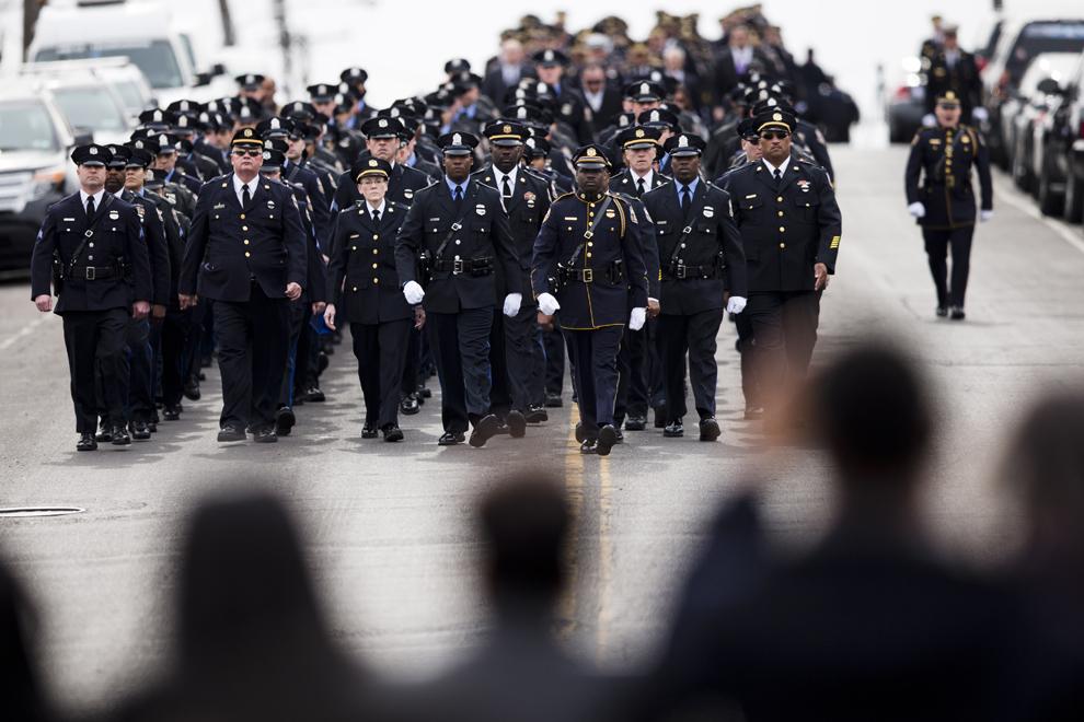 Membrii familiei ofiţerului de poliţie Robert Wilson al III-lea, ucis într-un schimb de focuri la un magazin de jocuri video, privesc spre reprezentanţi ai poliţiei ce mărşăluiesc spre priveghi, în Philadelphia, vineri, 13 martie 2015.