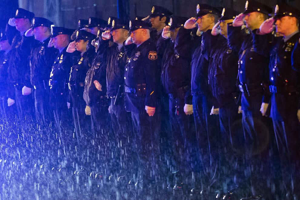 Ofiţeri de poliţie salută în timpul funeraliilor ofiţerului de poliţie Robert Wilson al III-lea, decedat într-un schimb de focuri la un magazin de jocuri video, în Philadelphia, sâmbătă 14 martie 2015.