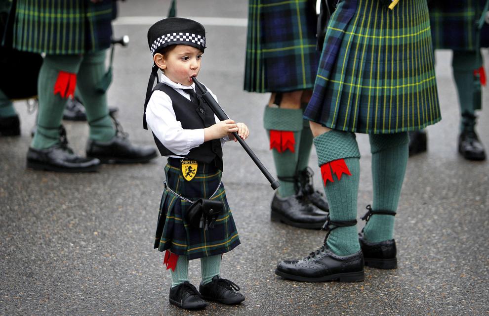 Rowan Miller, în vârstă de doi ani stă alături de bunicul său, în timp ce fanfara Shelby County Sheriff se pregăteşte de parada anuală de Sfântul Patrick, în Memphis Tenn, Irlanda, sâmbătă, 14 martie 2015.