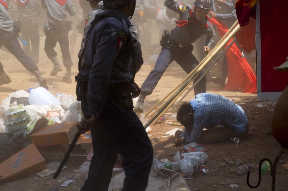 Un ofiţer de poliţie bate un elev protestatar, în Letpadan, 140 km nord de Yangon, Myanmar, marţi, 10 martie 2015.