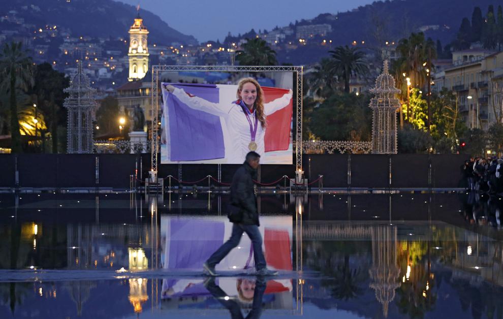 Un bărbat trece prin faţa unui poster afişat în memoria campioanei olimpice Camille Muffat, marţi, 10 martie 2015, în Nisa, sud-estul Franţei.