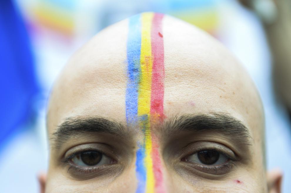 Un tânăr cu tricolorul pictat pe cap participă la un eveniment în cadrul căruia este format un lanţ uman din faţa sediului Ministerului Afacerilor Externe al României, până în faţa Ambasadei Republicii Moldova, pentru a solicita autorităţilor eliminarea paşapoartelor la trecerea frontierei peste Prut, în Bucureşti, duminică, 15 martie 2015.