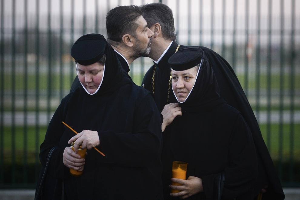 """Doi preoţi se sărută pe obraz în timp ce aşteaptă sosirea Episcopului vicar al Arhiepiscopiei Bucureştilor, Preasfinţitul Timotei Prahoveanul, care aduce Lumina Sfântă din Ierusalim, pe Aeroportul Internaţional """"Henri Coanda"""" din Otopeni, sâmbătă, 11 aprilie 2015."""