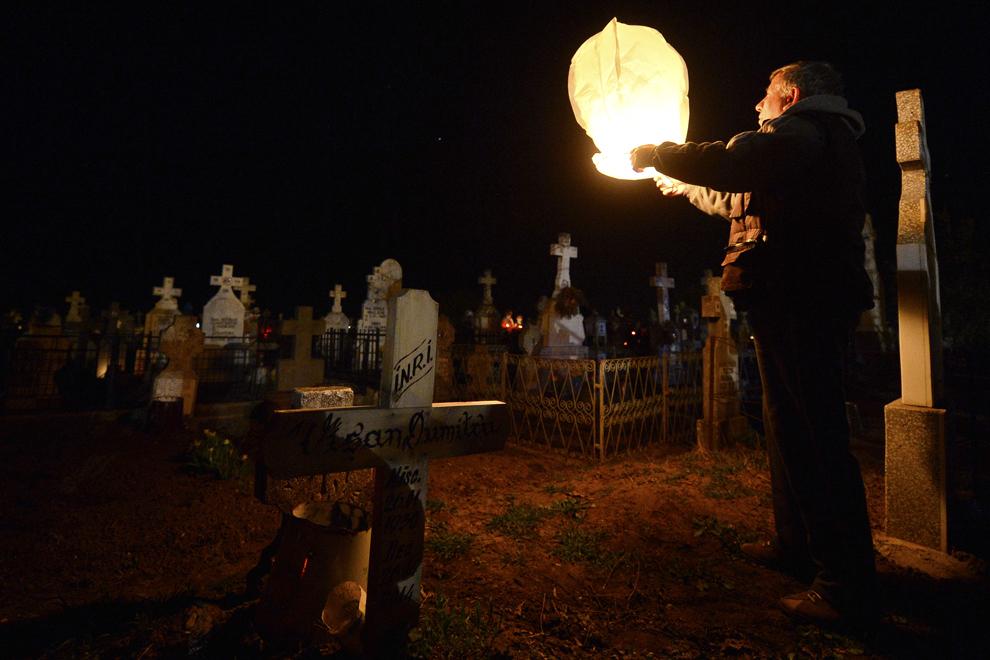 Un bărbat lansează un lampion în cimitirul bisericii din comuna Remus, judeţul Giurgiu, după slujba de Înviere, duminică, 12 aprilie 2015.