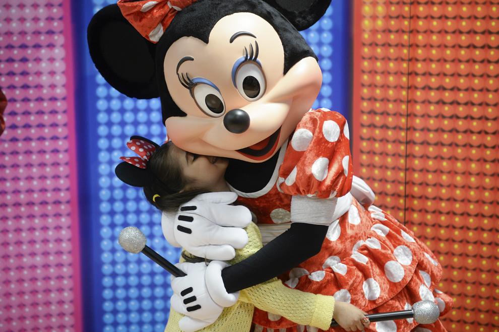 O fetiţă îmbrăţişează personajul Minnie Mouse, cu ocazia conferinţei de presă organizate înaintea spectacolului muzical Disney Live! Mickey's Music Festival, în Bucureşti, miercuri, 15 aprilie 2015.