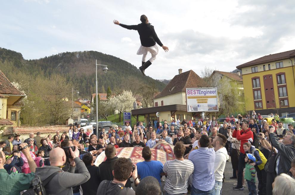 """Un tânăr este aruncat în aer, cu prilejul ritualului """"Aruncarea în ţol"""", eveniment organizat de Uniunea Junilor din Scheii Braşovului si Braşovul Vechi, în Piaţa Unirii (Prund), Braşov, vineri, 17 aprilie 2015. """"Aruncarea-n ţol"""", realizată prin intermediul Grupului Junilor Tineri, face parte din serbările tradiţionale ale Junilor din perioada Săptămânii Luminate, fiind la origine un vechi ritual de confirmare şi de iniţiere în ceata de feciori."""