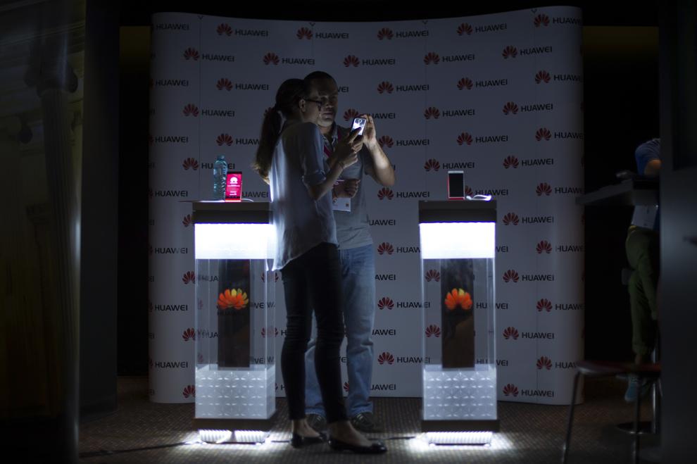 Două persoane testeaza un telefon Huawei în timpul festivalului dedicat industriei digitale şi interactive din Europa Centrală şi de Est, Interactive Central and Eastern Europe Festival 2015 (ICEEFest), în Bucureşti, joi, 11 iunie 2015.