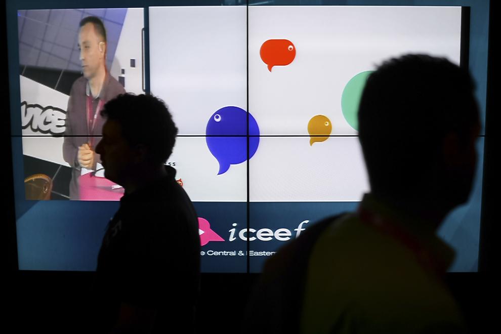 Două persoane trec prin dreptul unui ecran, în timpul festivalului dedicat industriei digitale şi interactive din Europa Centrală şi de Est, Interactive Central and Eastern Europe Festival 2015 (ICEEFest), în Bucureşti, joi, 11 iunie 2015.