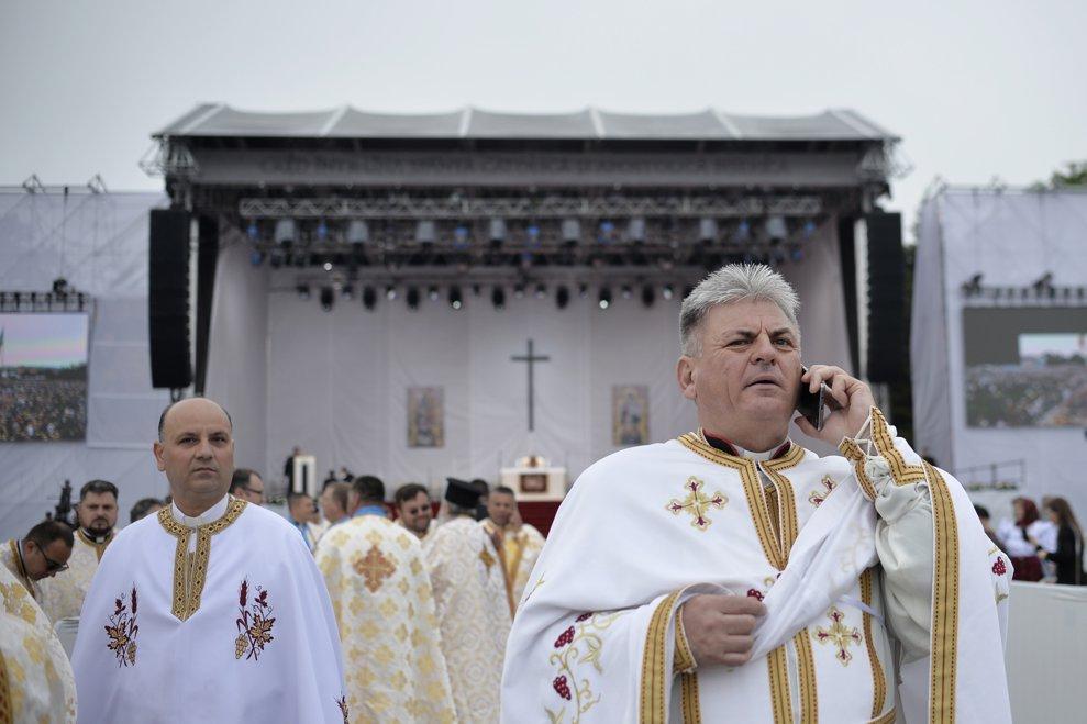Un preot vorbeste la telefonul mobil inainte de sosirea Suveranului Pontif, la Blaj. Zeci de mii de pelerini s-au strans pe Campia Libertatii din Blaj, pentru a participa, in ultima zi a vizitei pe care Papa Francisc o face in Romania, la ceremonia de beatificare a sapte episcopi greco-catolici martiri, duminica 2 iunie 2019. ANDREEA ALEXANDRU / MEDIAFAX FOTO