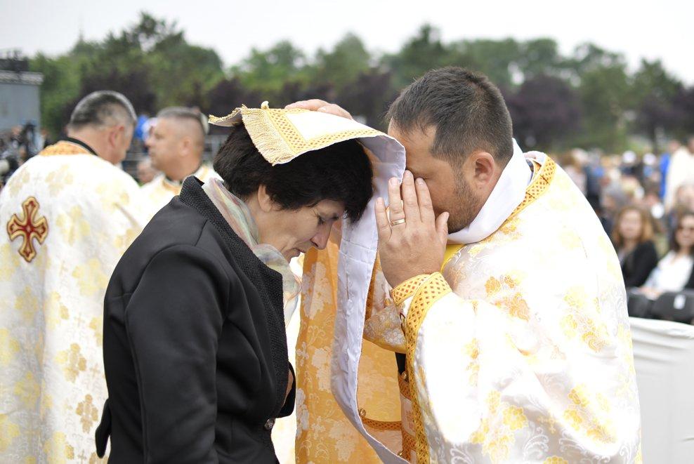 O femeie se impartaseste pe Campia Libertatii din Blaj, in ultima zi a vizitei pe care Papa Francisc o face in Romania, inaintea ceremoniei de beatificare a sapte episcopi greco-catolici martiri, oficiata de catre insusi Suveranul Pontif, duminica 2 iunie 2019. ANDREEA ALEXANDRU / MEDIAFAX FOTO
