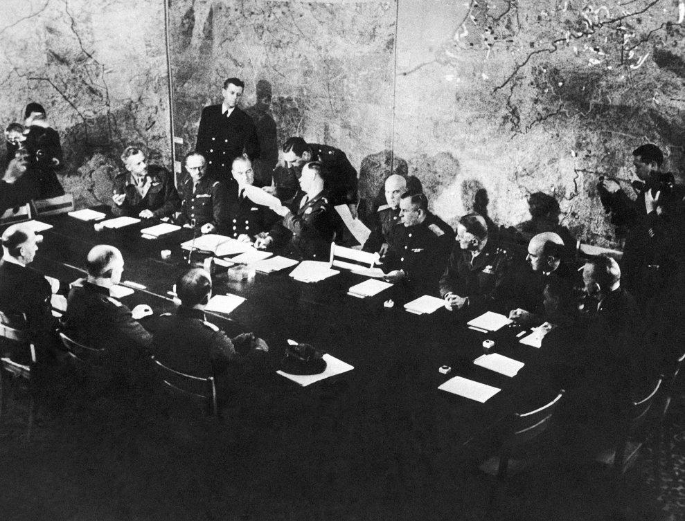 Reprezentaţi ai Germaniei şi ai Forţelor Aliate prezenţi în Camera de Război din Cartierul General Suprem din Reims, Franţa pe 7 mai 1945, unde delegaţii germani au capitulat necondiţionat în faţa Marii Britanii, URSS şi SUA.  Şedinţa istorică a avut loc la etaj în Şcola Modernă de Băieţi din Reims.  La masă, de la stangă la dreapta se află: Reprezentanţii Germaniei Wilhelm Oxenius, ajutor al generalului Alfred Jodl, şi generalul amiral Hans-Georg von Friedeburg,  generalul Frederick E. Morgan, generalul Francois Sevez, amiralul Harold Burrough, generalul Walter Bedell Smith, generalul Ivan Susloparov generalul Carl Spaatz, mareşalul aerian Sir James Milne Robb, generalul Harold R. Bull, colonelul Zenkovitch, ajutorul generalului rus Susloparov.(AP Photo/Morse)
