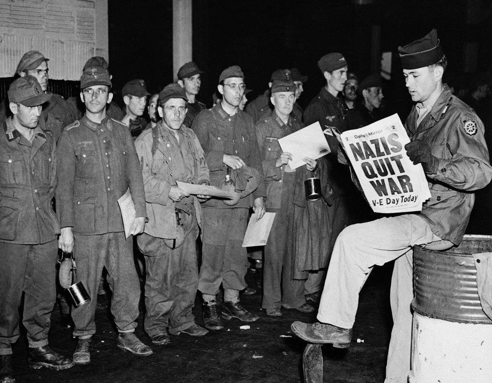 Soldatul american K. Ayers din Evansville, citeşte un ziar în timp ce prizonieri americani sosesc în portul din New York City, pe 8 mai 1945 (AP Photo/John Rooney)