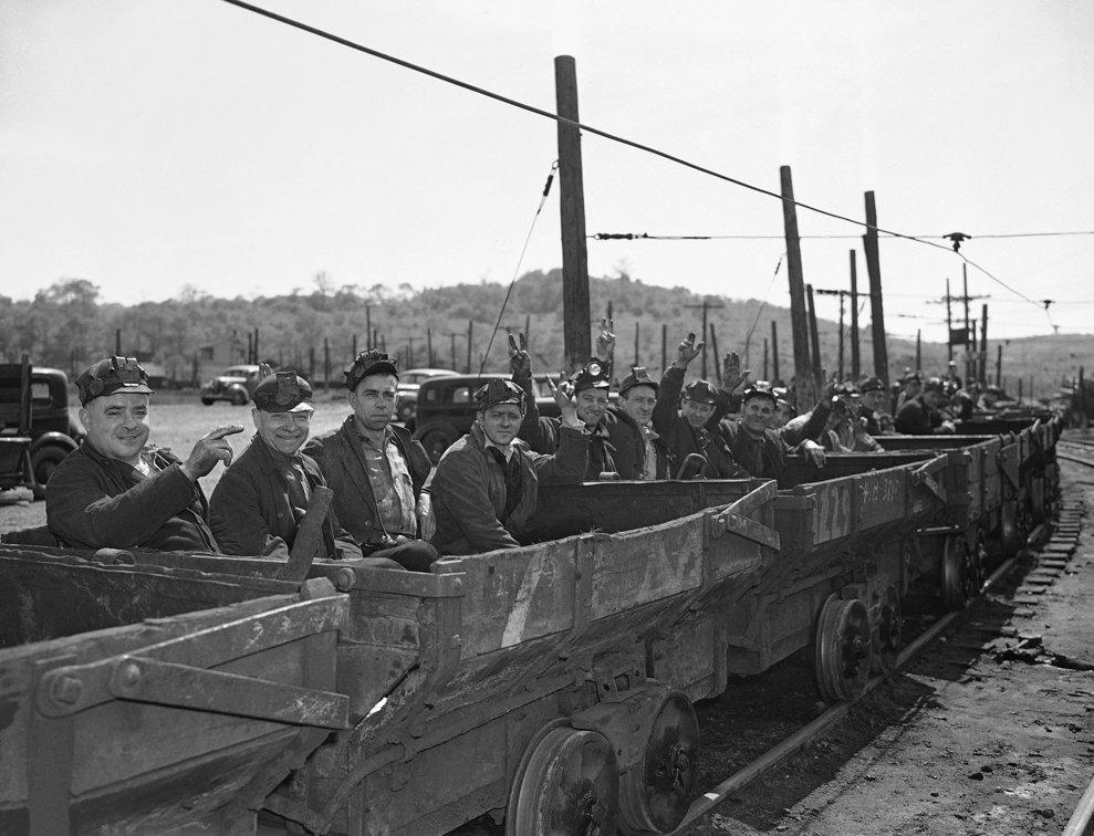 Mineri din Pittsburgh, SUA, reacţionează la vestea capitulării Germaniei, în drum spre muncă pe 8 mai 1945. Zâmbesc şi fac semnul victoriei.(AP Photo)