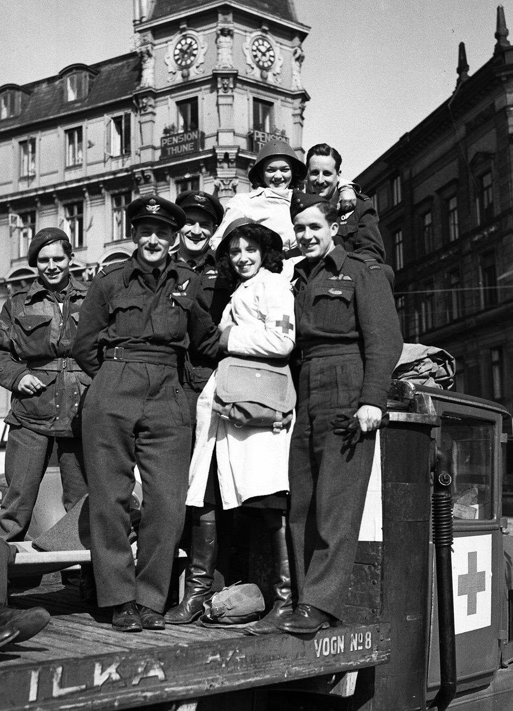 Piloţi din Forţa Regală Aeriană a Forţelor Armate Britanice şi asistente din Crucea Roşie, merg pe străzile din Copenhaga pe 8 mai 1945 pentru a sărbători capitularea Germaniei. (AP Photo/Eddie Worth)