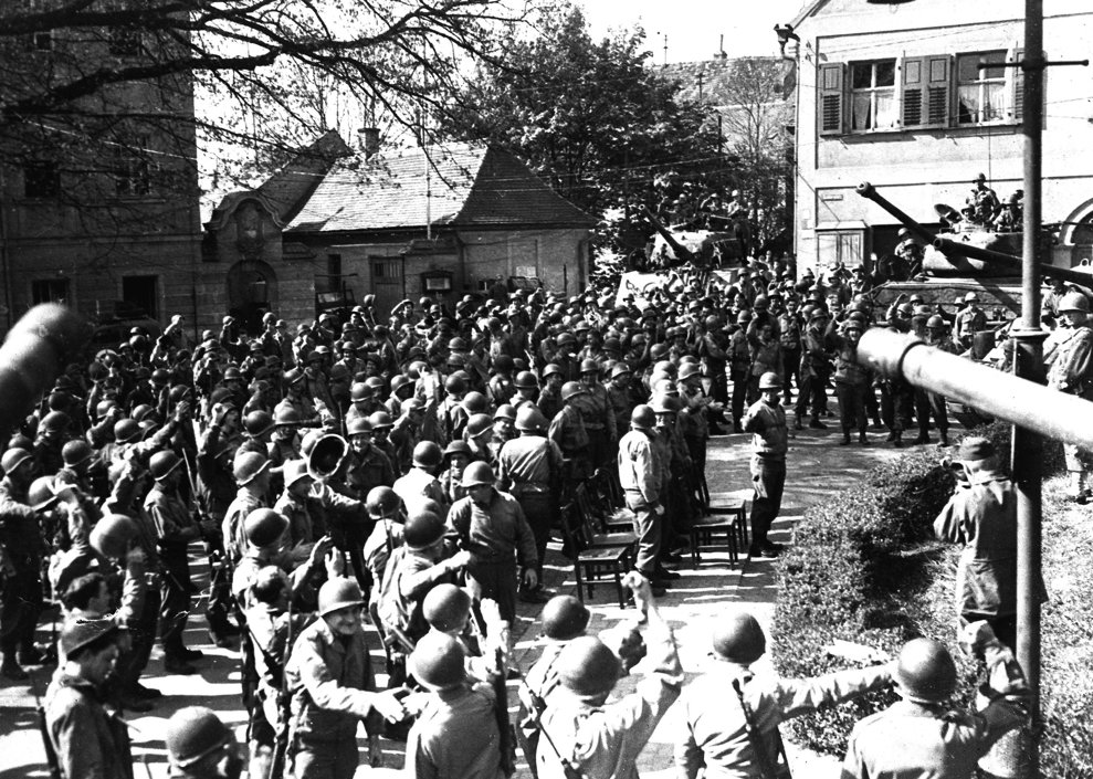 Soldaţi din a 9-a Diviziune blindată, prima armată a Statelor Unite, se felicită la aflarea veştii că Germania a capitulat, în piaţa centrală din Weiden, Germania, pe 9 mai 1945.(AP Photo/William C. Allen)