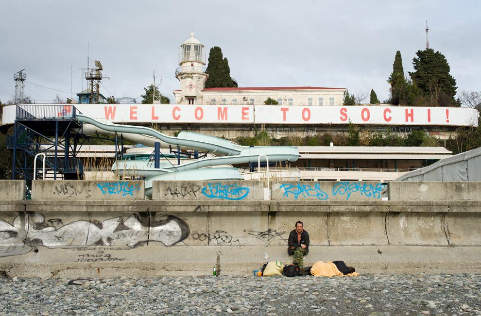 """Un bărbat stă alături de bunurile sale pe o plajă, sub un banner uriaş pe care scrie """"Bine aţi venit la Soci!"""", în centrul oraşului Soci, luni, 18 februarie 2013. Oraşul Soci va găzdui olimpiada de iarnă din 2014."""