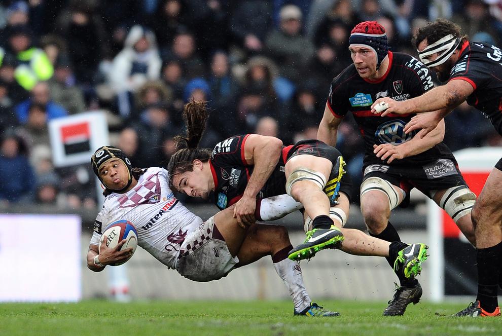 Heini Adams (S), de la Bordeaux-Begles, este atacat de Pierrick Gunther (C), de la Toulon, în timpul meciului din cadrul Ligii Franceze de Rugby Top 14, în Bordeaux, sâmbătăt, 9 februarie 2013.