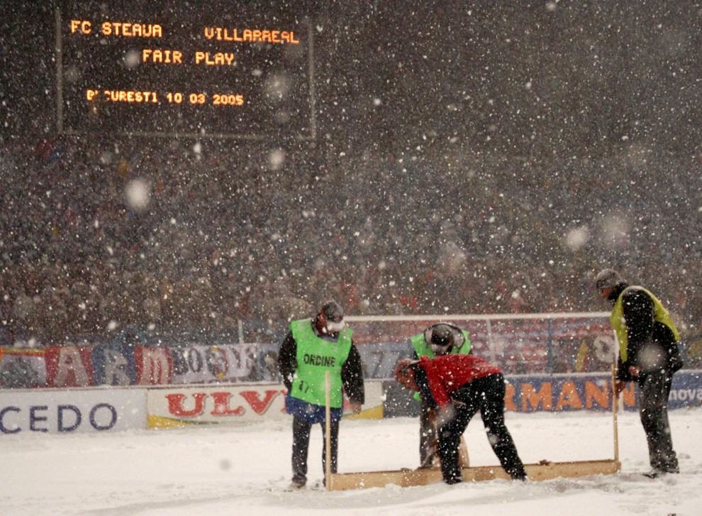 Mai mulţi angajaţi ai clubului Steaua încearcă să cureţe zăpada cazută înaintea partidei contra echipei Villarreal, joi, 10 martie 2005. Partida Steaua – Villarreal a fost amânată din cauza ninsorii abundente.