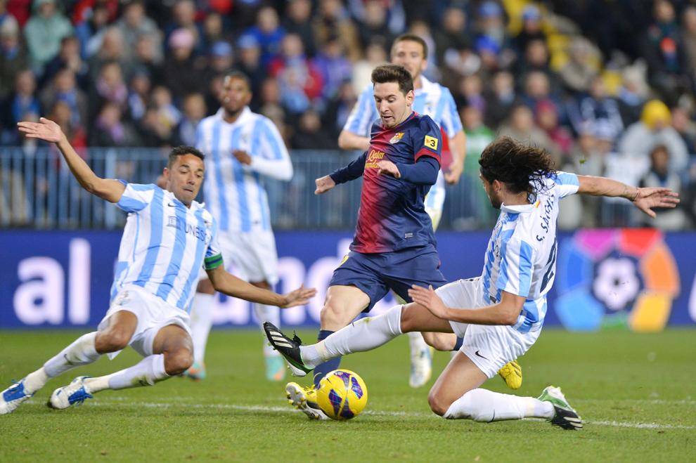 Lionel Messi (C), de la FC Barcelona, se luptă pentru balon cu Joaquín Sánchez (D), de la Malaga, în timpul meciului contând pentru etapa a XIX-a a campionatului Spaniei, disputat în Malaga, duminică, 13 ianuarie 2013.