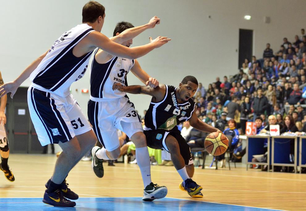 Kevin Sims (D), de la CSS Giurgiu, încearcă să treacă de doi adversari în timpul meciului de baschet masculin cu SCM U Craiova, în Craiova, duminică, 20 ianuarie 2013.