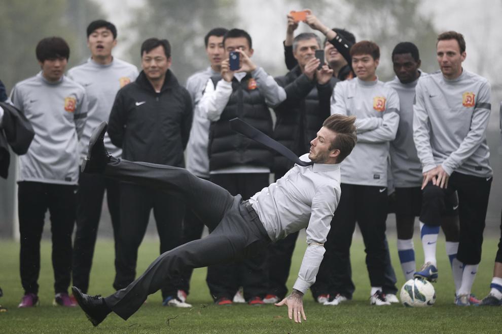 David Beckham se dezechilibrează şi cade în timpul vizitei sale la clubul de fotbal Wuhan Zall, în Wuhan, provincia Hubei, China, sâmbătă, 23 martie 2013.