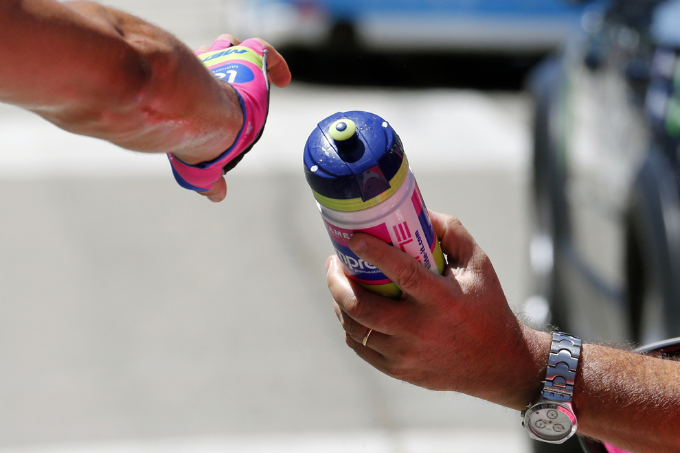 Un ciclist, membru al echipei Lampre – Merida, primeşte un bidon cu apă din partea echipei sale tehnice, în timpul celei de-a 6-a etape a Turului Franţei la ciclism, între Aix-en-Provence şi Montpellier, în sudul Franţei, joi, 4 iulie 2013.