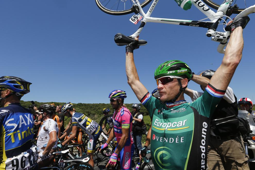 Francezul Thomas Voeckler (D) îşi ţine bicicleta ridicată deasupra capului după ce, urmare a unei căzături, ciclişti din pluton au blocat drumul, în timpul celei de-a 7-a etape a Turului Franţei la ciclism, între Montpellier şi Albi, în sud-vestul Franţei, vineri, 5 iulie 2013.