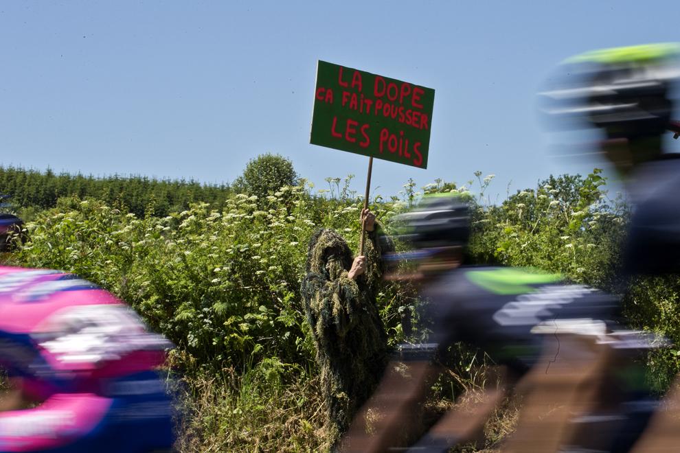 Ciclişti trec pe lângă un bărbat care ţine o pancartă pe care este scris 'Drogurile fac părul să crească', în timpul celei de-a 7-a etape a Turului Franţei la ciclism, între Montpellier şi Albi, în sud-vestul Franţei, vineri, 5 iulie 2013.