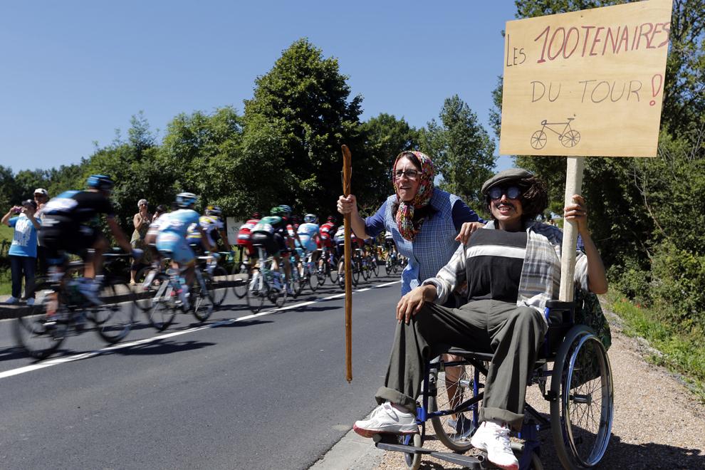 Spectatori deghizaţi în bătrâni încurajează cicliştii în timp ce afişează o pancartă pe care scrie 'Centenarii Turului!', în timpul celei de-a 8-a etape a Turului Franţei la ciclism, între Castres şi Ax 3 Domaines, în sud-vestul Franţei, sâmbătă, 6 iulie 2013.
