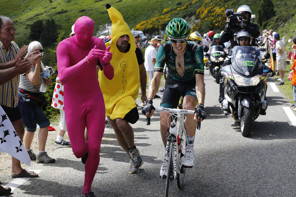 Francezul Pierre Rolland pedalează în timp ce suporteri deghizaţi aleargă alături de el în timpul celei de-a 8-a etape a Turului Franţei la ciclism, între Castres şi Ax 3 Domaines, în sud-vestul Franţei, sâmbătă, 6 iulie 2013.