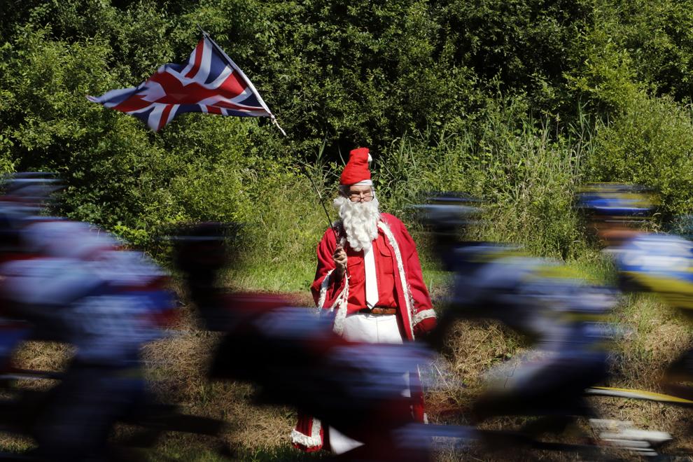 Un suporter deghizat în Moş Crăciun ţine în mînă un steag al Marii Britanii în timp ce cicliştii trec prin faţa lui, în timpul celei de-a 10-a etape a Turului Franţei la ciclism, între Saint-Gildas-des-Bois şi Saint-Malo, în nord-vestul Franţei, marţi, 9 iulie 2013.