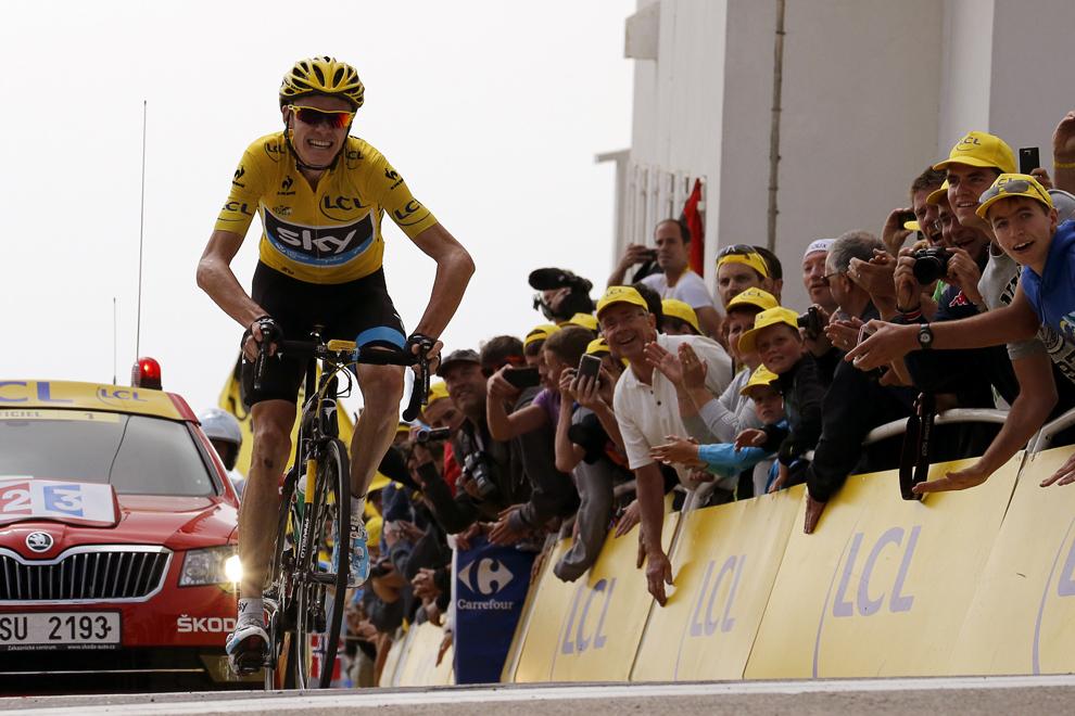 Liderul cursei şi purtător al tricoului galben, britanicul Christopher Froome celebrează trecerea liniei de sosire, la finalul celei de-a cincisprezecea etape a Turului Franţei, între Givors şi Mont Ventoux, sud-estul Franţei, duminică, 14 iulie 2013.
