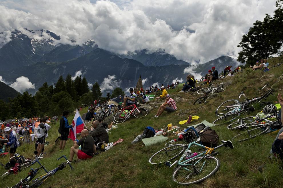 Spectatori aşteaptă ciclistii ce pedalează în timpul celei de-a 18-a etape a Turului Franţei, între Gap şi Alpe-d'Huez, în Alpii Francezi, joi, 18 iulie 2013.