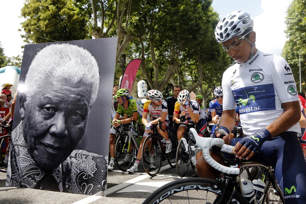 Deţinătorul tricoului alb, lider pentru ciclistii sub 26 de ani, columbianul Nairo Quintana (D) stă lângă un portret înfăţişându-l pe fostul preşedinte sud– african, Nelson Mandela, la kilomentrul zero, înaintea startului celei de-a 18-a etape a Turului Franţei, între Gap şi Alpe-d'Huez, în Alpii Francezi, joi, 18 iulie 2013.