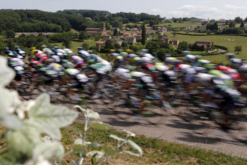 Un grup de ciclişti trece prin satul Chandon din zona central-estică a Franţei, în timpul celei de-a paisprezecea etape a Turului Franţei, între Saint-Pourcain-sur-Sioule şi Lyon, sâmbătă, 13 iulie 2013.