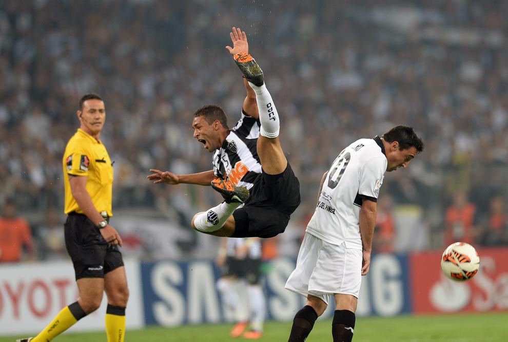 Brazilianul Pierre (C) de la Atletico Mineiro sare la balon lângă Juan Salgueiro (D) de la Olimpia, în timpul meciului de fotbal contând pentru Cupa Libertadores, în Belo Horizonte, Brazilia, miercuri, 24 iulie 2013.