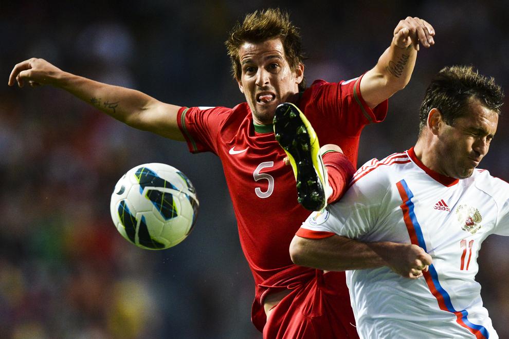 Fundaşul Portugaliei, Fabio Coentrao (S) se luptă pentru balon cu jucătorul Rusiei, Aleksandr Kerzhakov în timpul meciului de calificare Portugalia vs Rusia pentru World Cup 2014, pe stadionul Da Luz, din Lisabona, Portugalia, vineri, 7 iunie 2013.